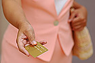Woman in Pink is Giving a Gold Credit Card