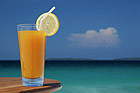 Glass of Juice with Lemon Twist and Straw Against Tropical Sea.